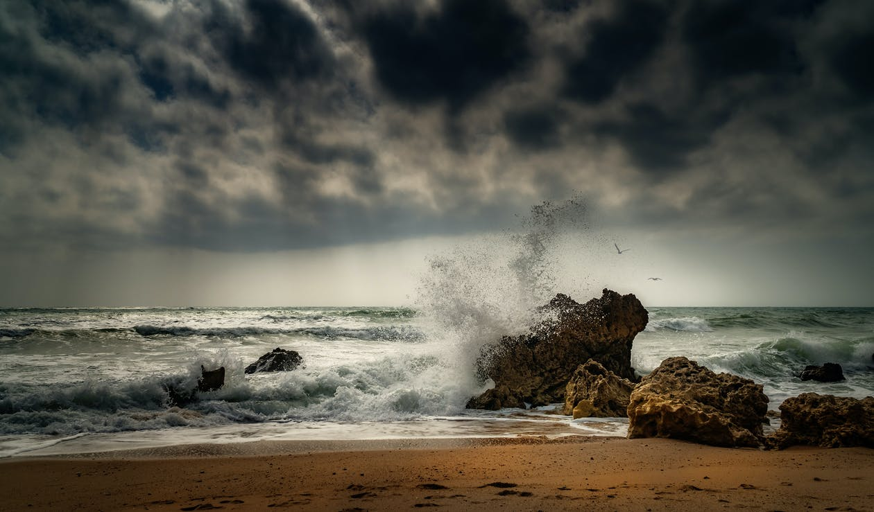 Ocean Waves Crashing on Brown Rock Formation Under Gray Clouds