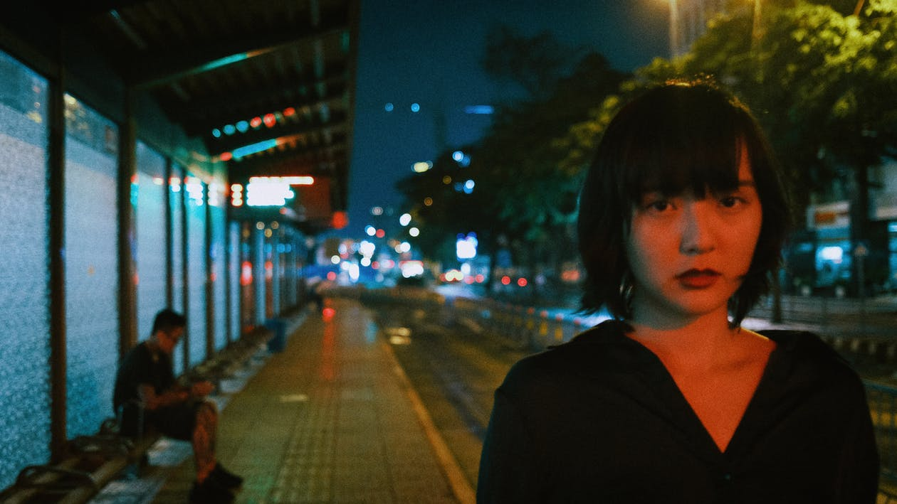 Young Asian woman on station at night