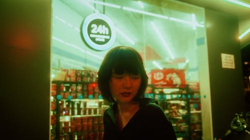 Young Asian female standing near illuminated window of store at night in city