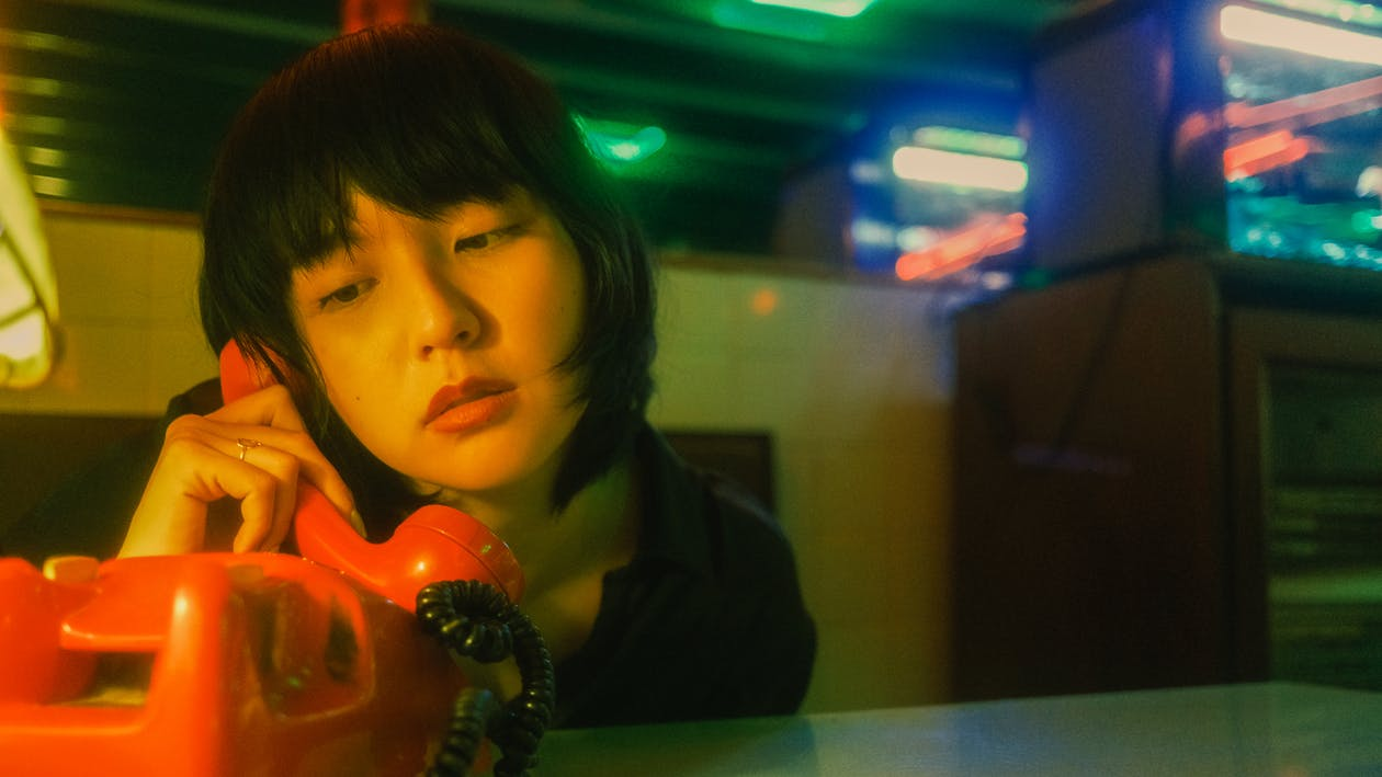 Sad young Asian female calling on retro telephone