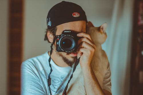 Young man with cat and taking photo on camera