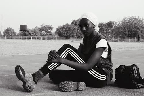 Black and white of African American sportswoman in headscarf and sportive clothes sitting on track with bag looking at camera