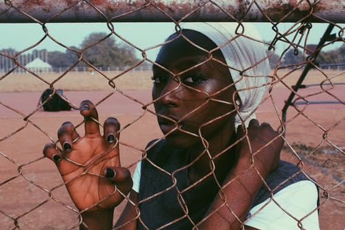 Black thoughtful woman wearing white turban standing behind wire fence on sports ground looking at camera