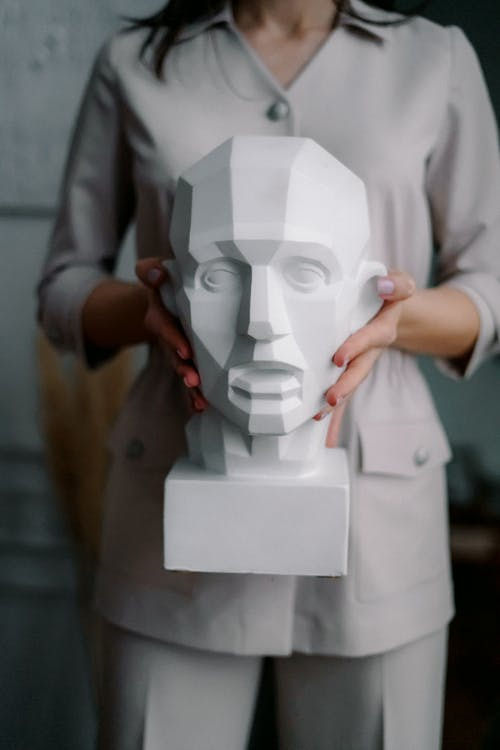 Unrecognizable woman holding handmade sculpture in hands