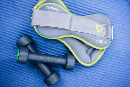 From above of modern dumbbells and leg weight belts placed on blue fitness mat in studio