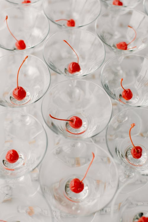 Refreshing alcoholic drinks with cherries served on white table