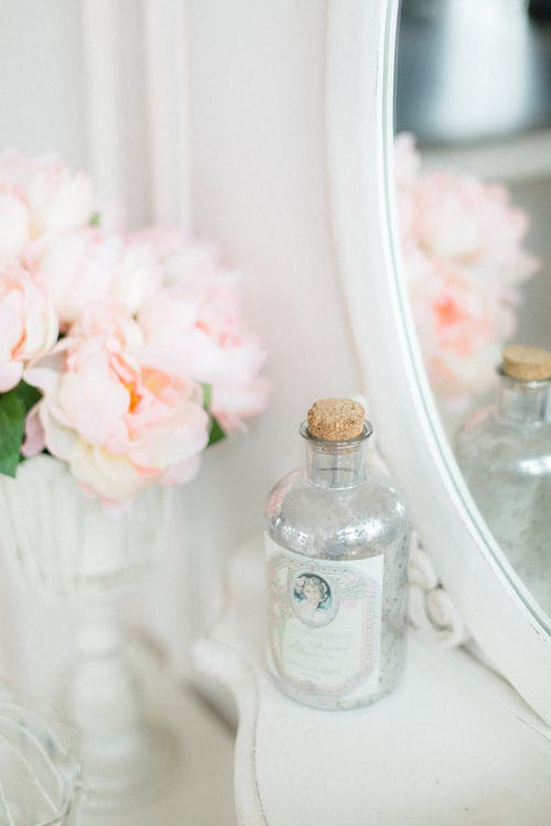 Decorative bottle and vase with aromatic pink flowers placed on white table