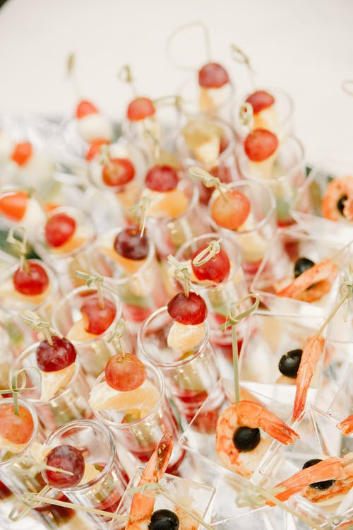 From above of rows of appetizers with grapes and shrimps in glassware served on white table