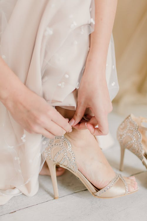 Bride in wedding dress putting shoes on