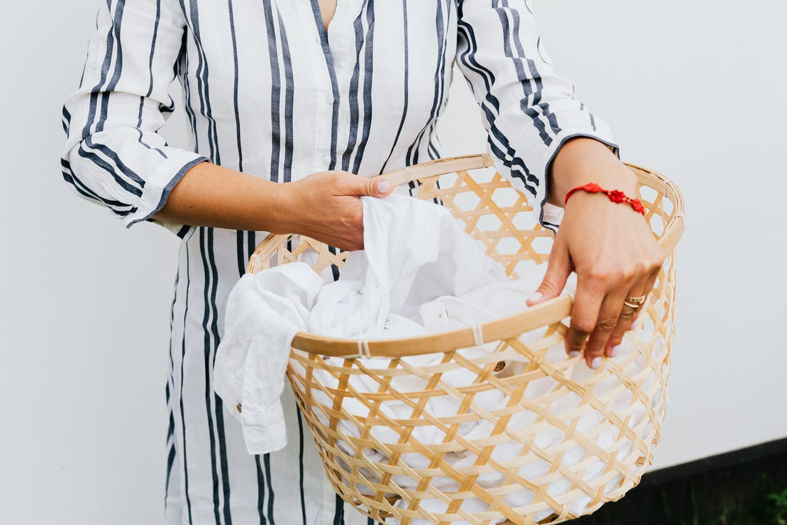 Woman in Blue and White Dress Shirt Holding Brown Woven Basket