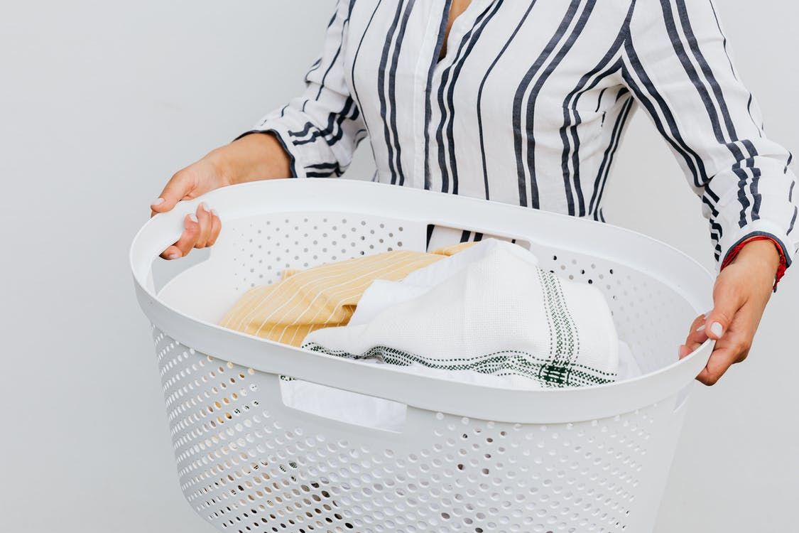 Woman in Black and White Stripe Long Sleeve Shirt Holding White Plastic Laundry Basket