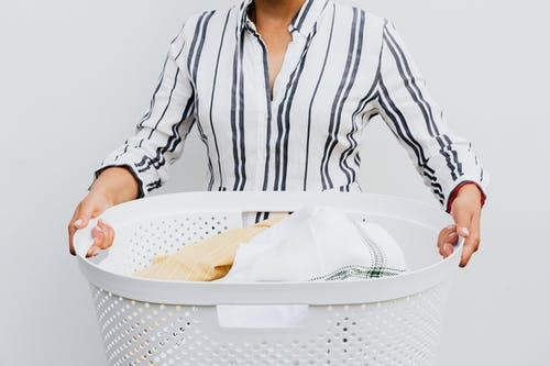 Woman in White and Black Stripe Long Sleeve Shirt Holding White Plastic Basket