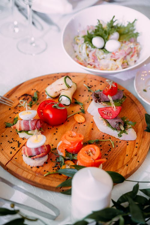 Wooden plate with various appetizers made of vegetables and meat