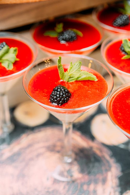 Delicious dessert in cocktail glasses with berries and mint leaves