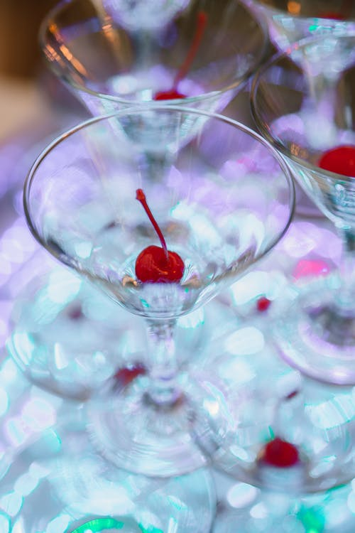 Cocktail glasses with cherry on transparent table