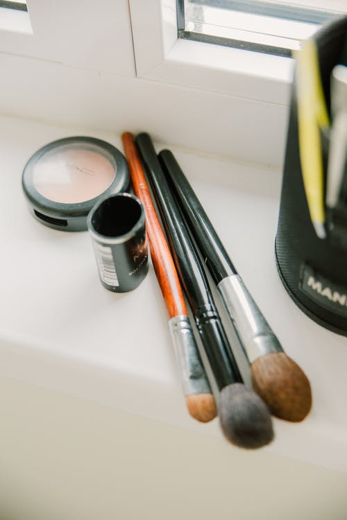 Makeup brushes with powder on windowsill