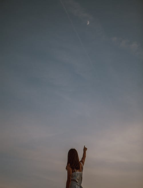 Woman pointing at sunset sky in evening