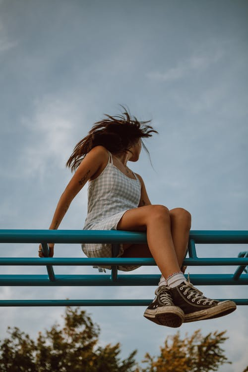 Woman in White Tank Top and Black and White Striped Shorts Sitting on Blue Metal Railings