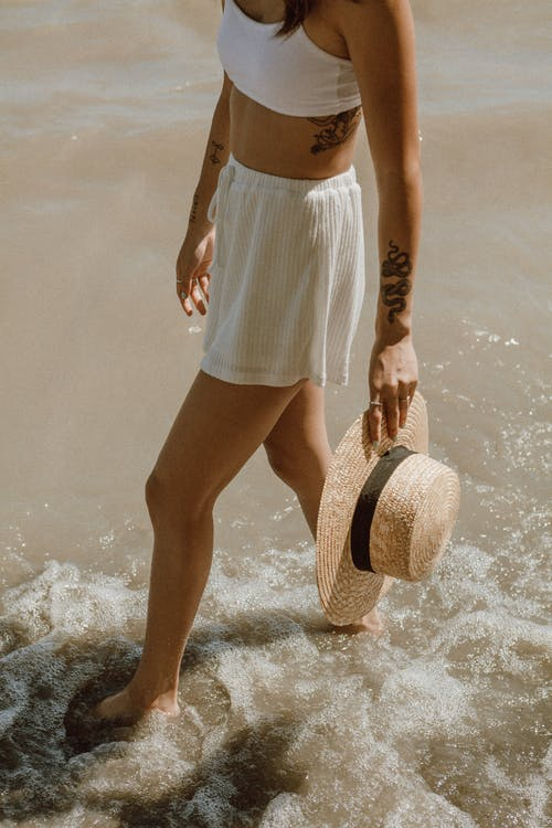 Woman in White and Blue Stripe Skirt and Brown Sun Hat Standing on Water