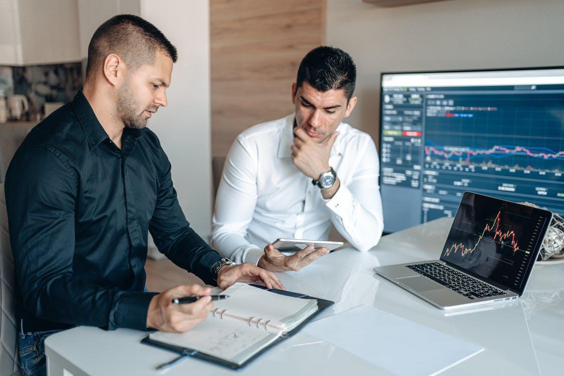 Man in Black Suit Jacket Holding Smartphone Beside Man in White Dress Shirt