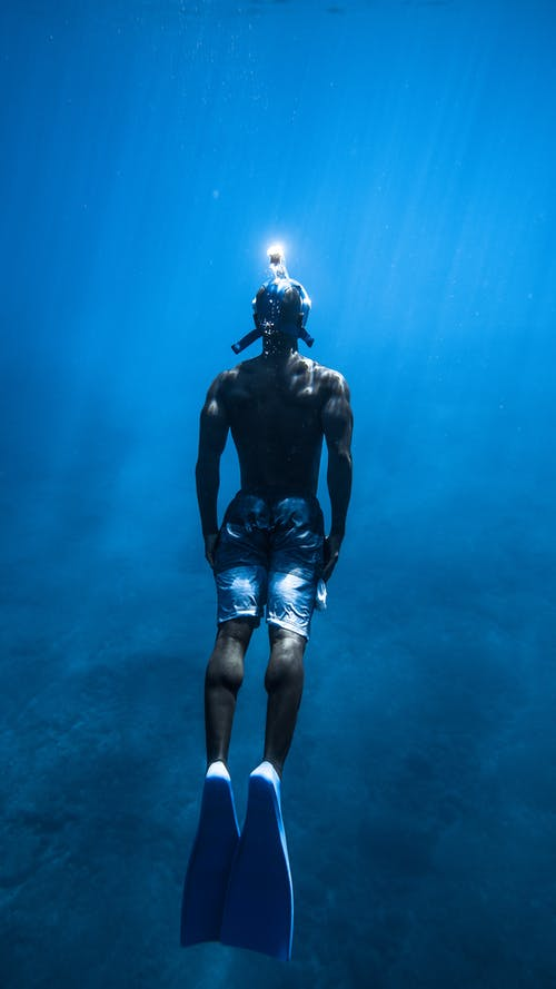 Unrecognizable man diving in blue water