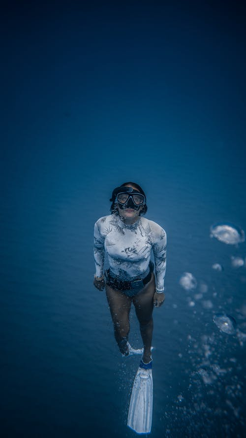 Unrecognizable woman in mask in deep water