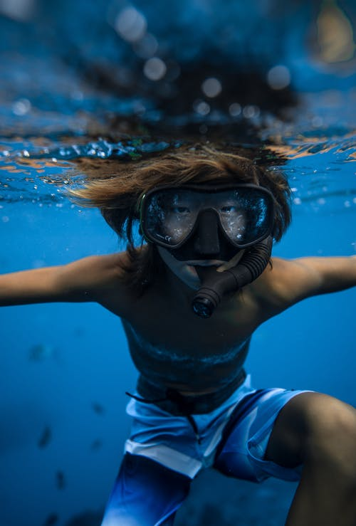 Boy snorkeling in mask underwater