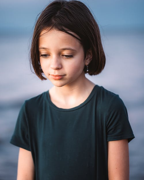Pensive little girl with short hair wearing t shirt looking down while standing on blurred background