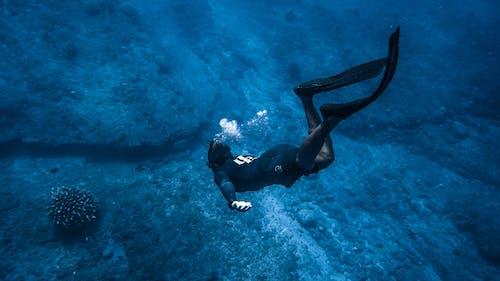 Unrecognizable person diving above rocks