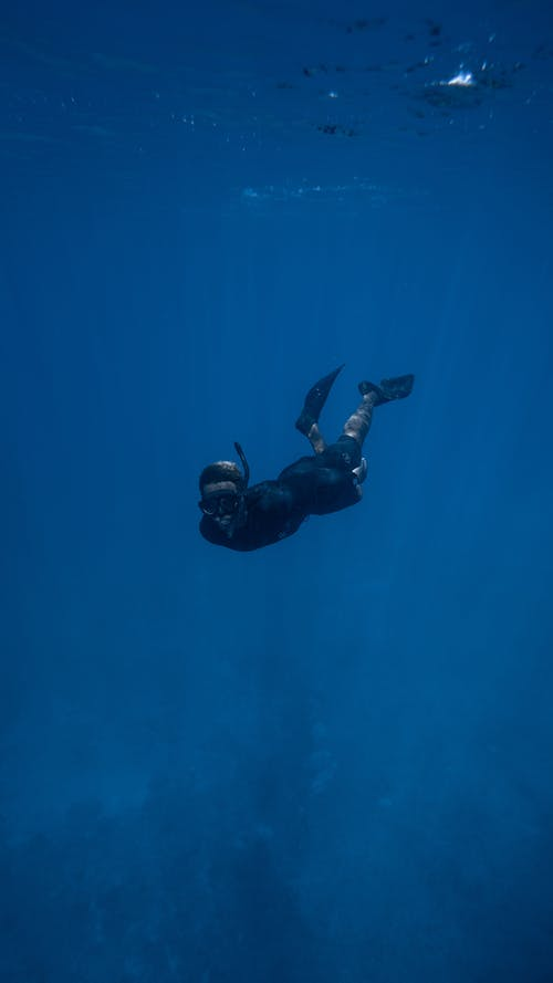Unrecognizable diver in wetsuit and mask with tube swimming underwater in deep ocean with bubbles on surface in tropical country
