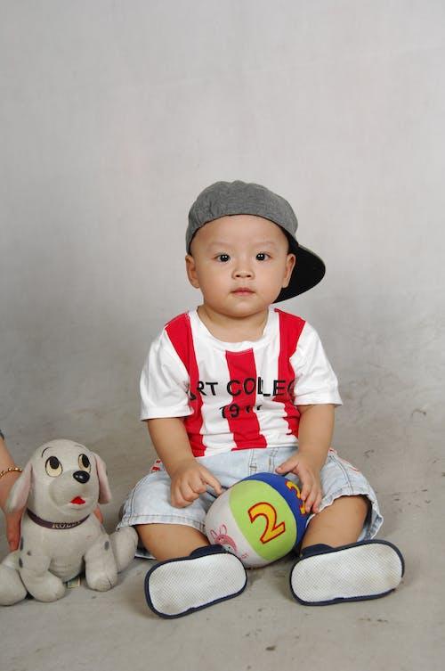 Бесплатное стоковое фото с Азиатский ребенок, держать, кепка