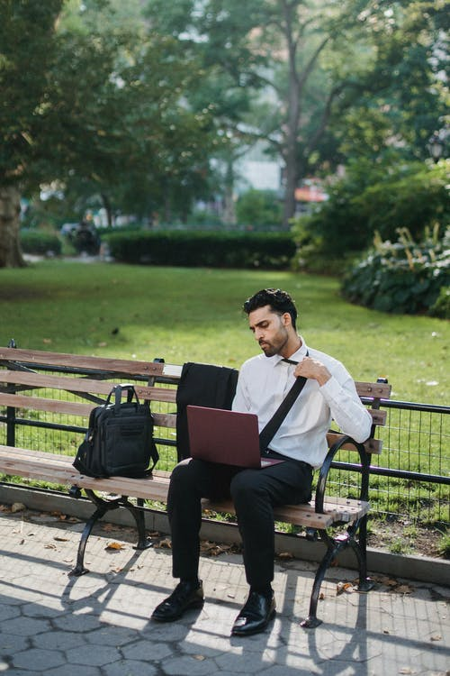 A Man in a White Long Sleeves Sitting on a Bench While Using a Laptop Computer