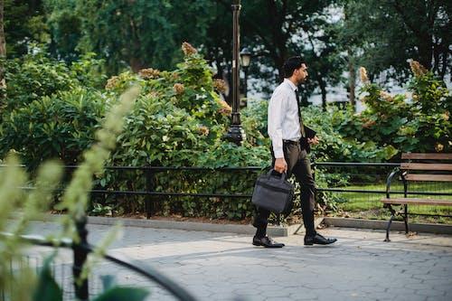 Fotos de stock gratuitas de bolso negro, hombre barbudo, hombre caminando