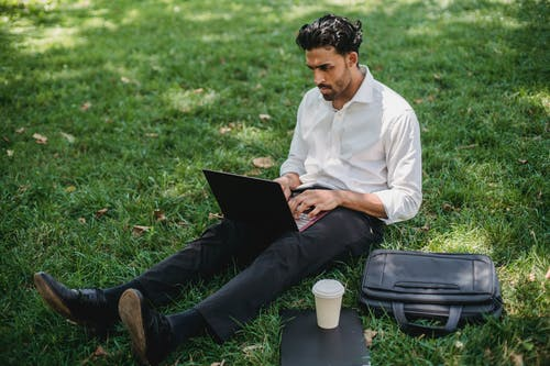 A Businessman Sitting on Grass while Using His Laptop