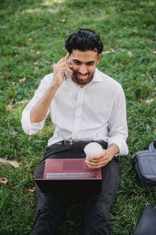 A Businessman Sitting on Grass while Having a Phone Call