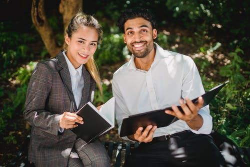 Two Happy Business People Looking at Camera