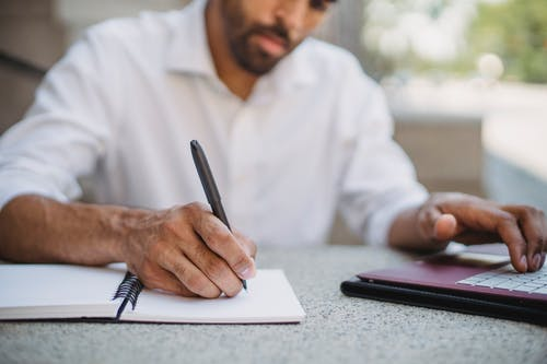 Shallow Focus Photo of a Person Writing on a Notebook while Using His Laptop