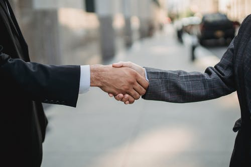 Man in Black Suit Holding Hands With Man in Black Suit