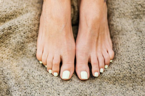 Persons Feet With Brown Nail Polish