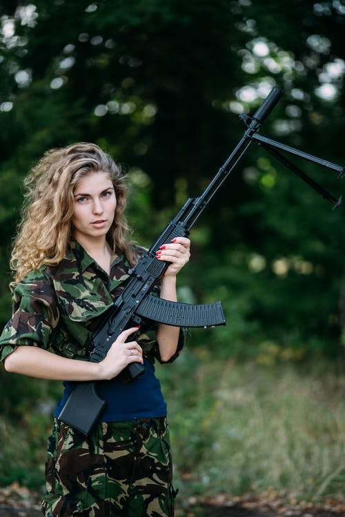 Woman in Green and Black Camouflage Jacket Holding Rifle