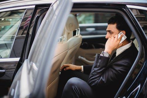Man in Black Long Sleeve Shirt and Black Pants Sitting on Car Seat