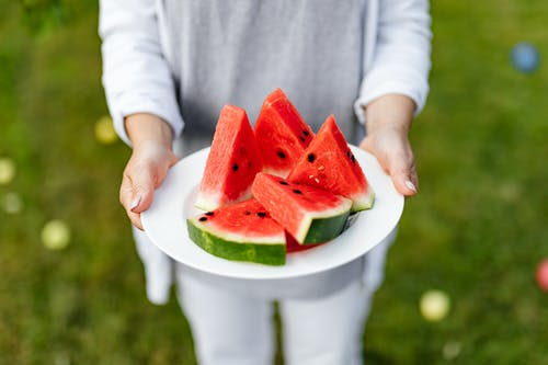 Person Holding Sliced Watermelon on White Ceramic Plate
