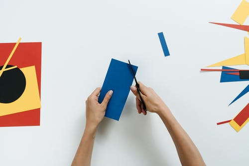 Person Holding Blue Paper With Red Pen