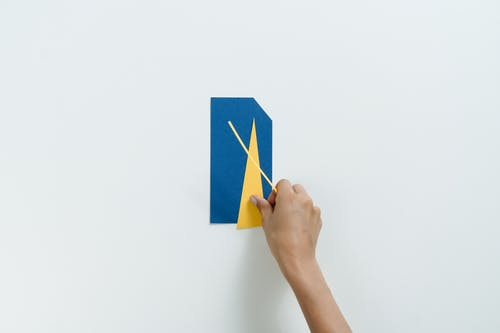 Person Holding Blue and Yellow Paper