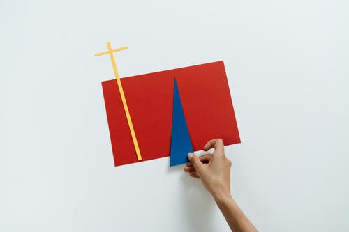 Person Holding Red and Blue Paper