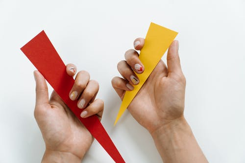 Person Holding Red and Yellow Paper