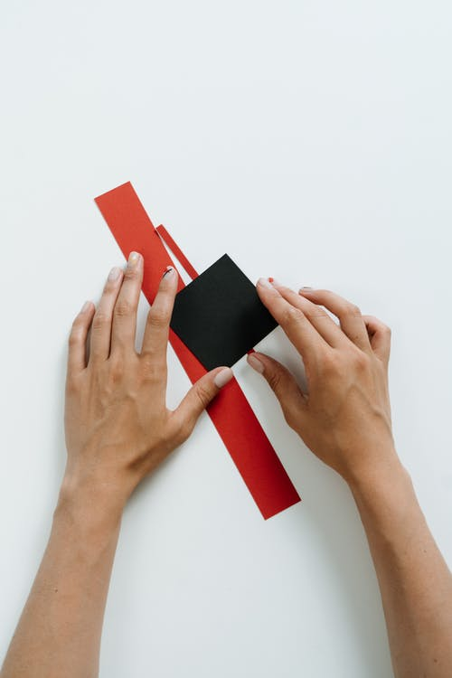 Person Holding Red and Black Card