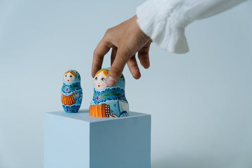 Person Holding White and Blue Snowman Figurine