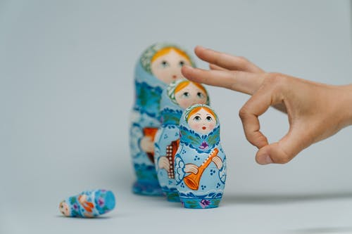 Person Holding Blue and White Ceramic Owl Figurine