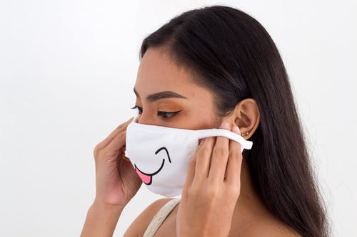 Woman in White Tank Top Covering Face With White Mask